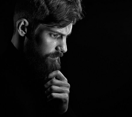 Black and white portrait of puzzled young man touching beard looking down over black background